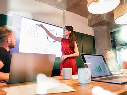 Female faculty teaching students on digital screen